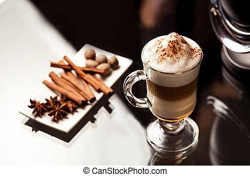 Latte macchiato spices on white plate (cinnamon, anise star and nutmeg)