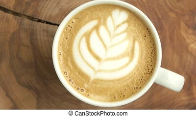 Latte with flower picture. Coffee cup spinning, top view....