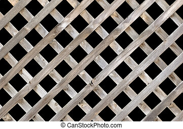 A lattice wooden fence isolated on black.