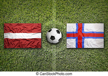 Latvia and Faroe islands flags on soccer field