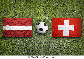 Latvia vs. Switzerland flags on soccer field - Latvia vs....