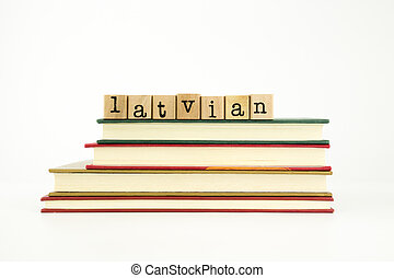 latvian word on wood stamps stack on books, foreign language and translation concept