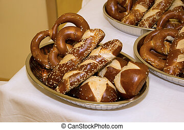 Laugen pretzels and sticks in bowls on a table with white tablec