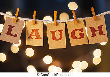 The word LAUGH printed on clothespin clipped cards in front of defocused glowing lights.