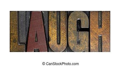 The word LAUGH written in vintage letterpress type