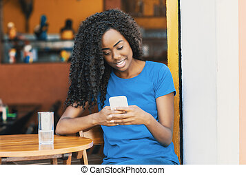 Laughing african american woman at bar texting message with mobile phone