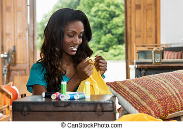 Laughing african american woman repairing clothes