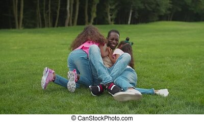 Laughing african dad and girls having fun outdoors - ...
