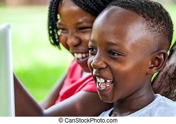 Laughing African kids looking at laptop screen.