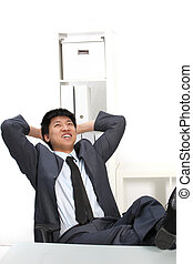 Laughing Asian businessman with his feet up