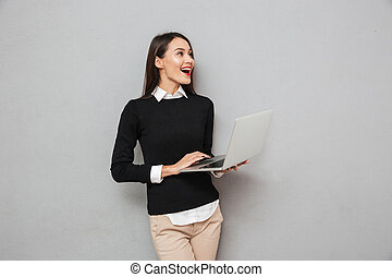 Laughing asian woman in business clothes using laptop computer