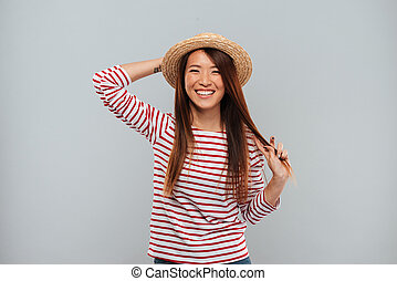Laughing asian woman in sweater and hat looking at camera
