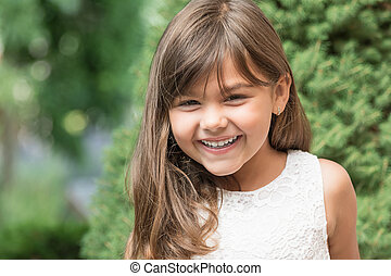 Laughing attractive little girl outdoors