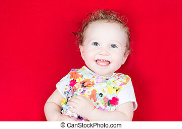 Laughing baby girl in a floral colorful dress