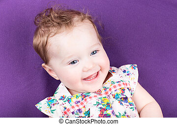 Laughing baby girl on a purple blanket