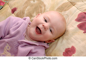 Laughing baby girl on bed, looking at mother.