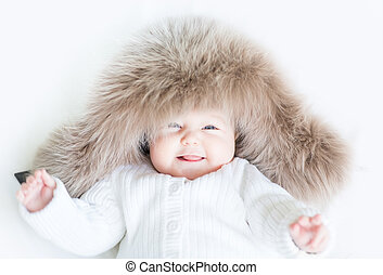 Laughing baby in a big fur hat