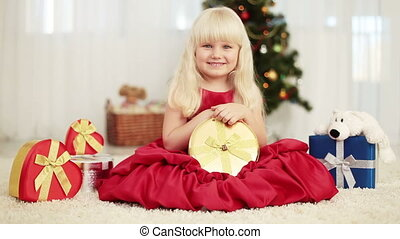 Laughing baby is holding a gift