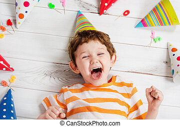 Laughing baby lying on the wooden floor with festive caps and candles on a carnival party.
