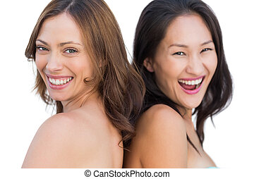 Laughing beautiful nude models posing back to back