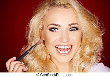 Laughing beautiful woman applying blusher to her cheek with a large cosmetic brush as she glances sideways at the camera