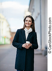 Laughing beautiful woman with cup of coffee in city street