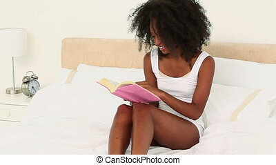 Laughing black haired woman reading a book while sitting on...