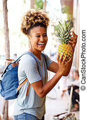 Laughing black woman standing outdoors with pineapple