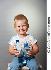 Laughing blond boy with bottles of water sitting on gray