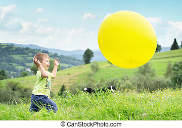 Laughing boy chasing a balloon