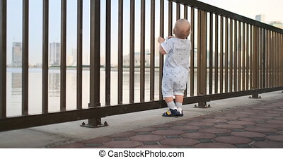 laughing boy dancing holding on to the railing - Laughing...