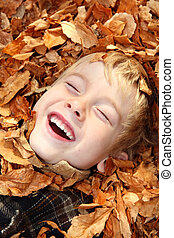 Laughing boy in a pile of leaves
