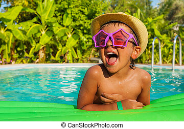 Laughing boy in star-shaped sunglasses on airbed