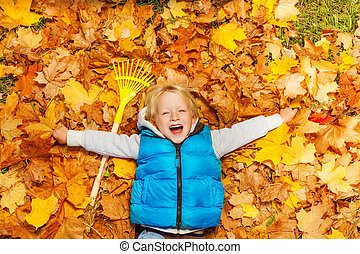 Laughing boy laying on the autumn leaves with rake