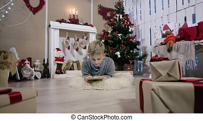 Laughing boy playing on digital tablet, The camera moves on a boy, white Room with Fireplace and Christmas Tree