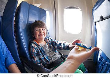 Laughing boy take toy plane, sit in jet airplane