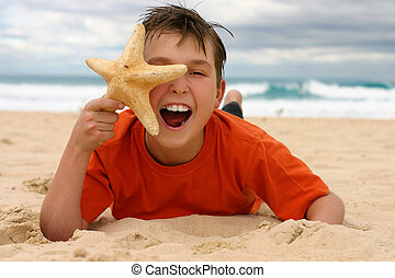 Laughing boy with starfish on the beach - Ecstatic child...
