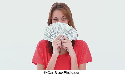 Laughing brunette haired woman holding US dollars