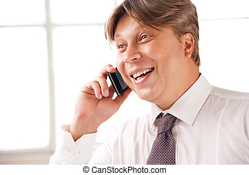 Laughing businessman on the phone in his office