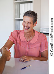 Laughing businesswoman shaking hands at desk