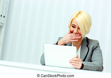 Laughing businesswoman sitting at the table and holding tablet computer in office