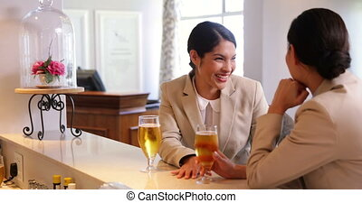 Laughing businesswomen having a beer