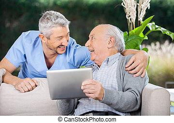 Laughing Caretaker And Senior Man Using Tablet Computer -...