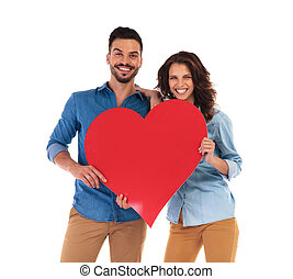 laughing casual couple holding a big red heart