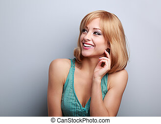 Laughing casual young blond woman looking up. Closeup portrait