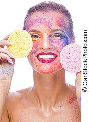 Laughing Caucaisan Girl With Colorful Artistic Powder Makeup Over Face and Shoulders Posing With Two Cleaning Sponges On White. Vertical Composition