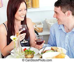 Laughing caucasian couple having dinner at home