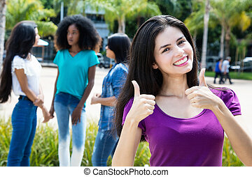 Laughing caucasian woman showing both thumbs with group of girlfriends