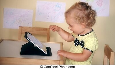 Laughing child girl touch tablet computer screen sitting near table