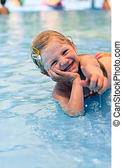 laughing child lying in the shallow water